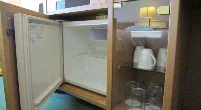 Tủ lạnh và ly, tách được sắp xếp gọn gàng, sạch sẽ.